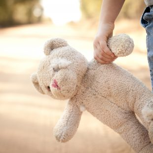 Child holding teddy bear by arm