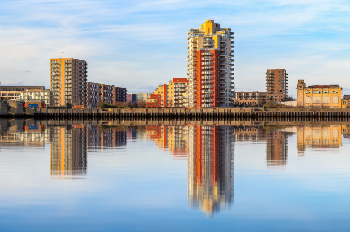 Riverside apartment next to Thames Barrier with its reflection from river Thames at sunset